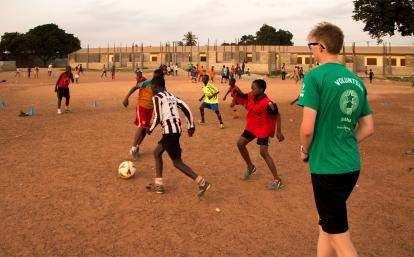 A Projects Abroad volunteer work with teens to teach football in Ghana.
